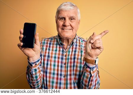 Senior handsome hoary man holding smartphone showing screen over yellow background very happy pointing with hand and finger to the side