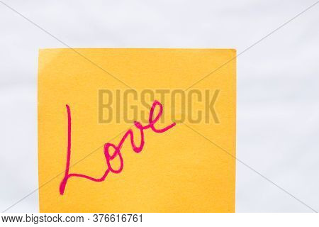 Love Handwriting Text Close Up Isolated On Orange Paper With Copy Space. Writing Text On Memo Post R