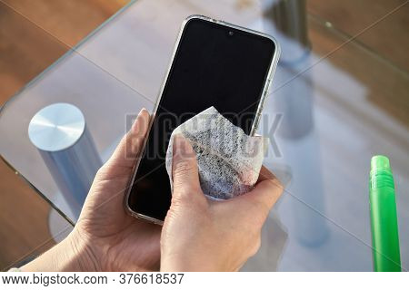 Woman Is Cleaning A Smartphone With A Jet Of Alcohol Aerosol Hand Sanitizer And Disposable Cloth At