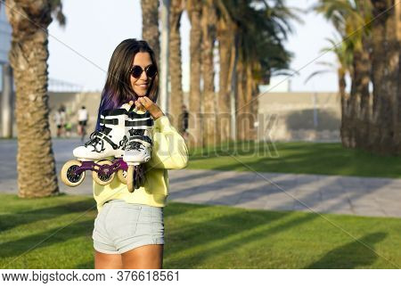 Young Beautiful Fit Girl With Blue Hair And Sunglasses Standing On Grass In Park, Turning Around Fro