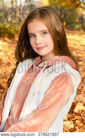 Autumn Portrait Of Smiling Little Girl Child In Leaves In The Park Outdoors