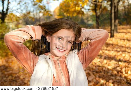 Autumn Portrait Of Happy Smiling Little Girl Child In Leaves In The Park Outdoors