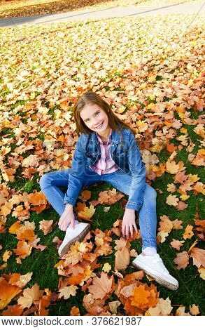 Autumn Portrait Of Happy Smiling Little Girl Child Sitting In Leaves In The Park Outdoors