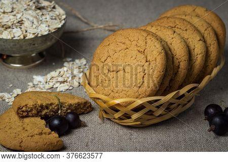 Oatmeal Cookies In A Wicker Basket. Broken Oatmeal Cookies Lie Nearby. Oatmeal In The Background