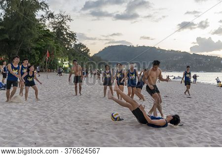 Thailand, Phuket, March 30, 2020: Men And Teenage Girls Play Soccer And Rugby With A Ball On The Bea
