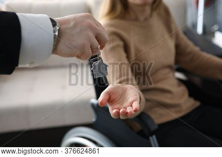 Close-up Of Male Businessman Giving Keys From New House To Disabled Woman. Lady Sitting In Wheelchai