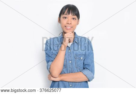 young woman in jeans shirt with blue jeans  standing with hand on chin thinking about question on white background,