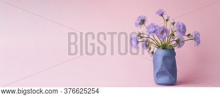 Bright Purple Wild Flowers Daisies On A Pink Background. Summer Spring Simple Bouquet. Vertical Phot