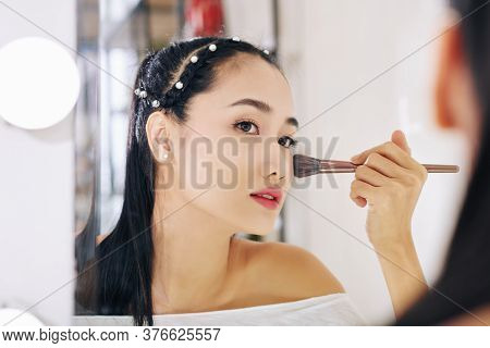 Beautiful Young Asian Woman Looking At Mirror And Applying Loose Face Powder On Her Cheeks