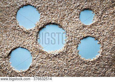Background With Natural Dry Rolled Oats With Five Copy Spaces In Shape Of Circles On Blue Paper. Sou