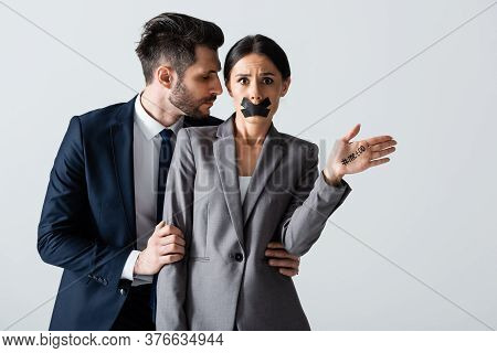 Businessman In Formal Wear Molesting Businesswoman With Scotch Tape On Mouth Showing Hand With Me To