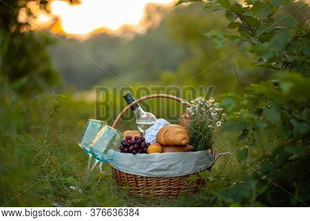 Basket With Wine, Bread And Fruit. Picnic.basket With Food In Nature. Background - A Basket Of Food