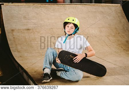 Portrait Confident, Cool Young Female Skateboarder At Outdoor Skate Park. Urban Girl With Skate Boar