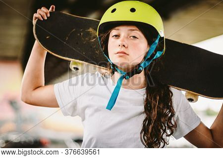 Close Up Of Young Attractive Girl With Skateboard Standing Outdoors In Skate Park. Female Skateboard
