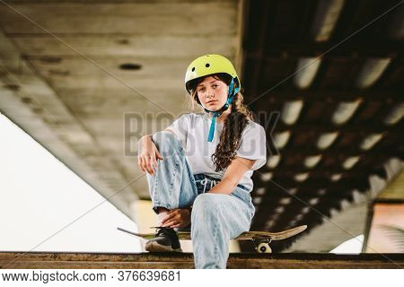 Schoolgirl After Lessons At Skateboarding Practice In Outdoor Skate Park. Stylish And Beautiful Cauc