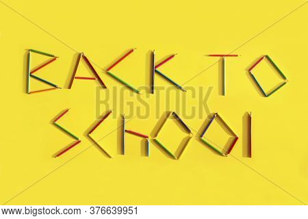 Words Back To School From Pencils On A Yellow Background. Back To School Concept. Flat Lay, Vertical