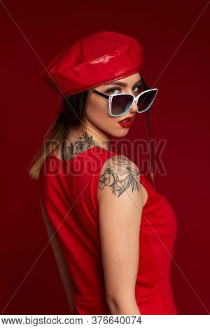 Beauty Brunette Young Woman In White Sunglasses, Hat And Dress Posing On Red Background. Girl Lookin