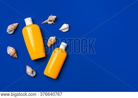 Bottles With Sunblock Cosmetics And Seashells On Dark Blue Background