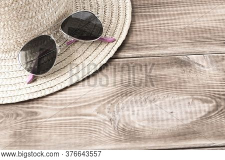 Sunglasses On A Straw Hat On A Wooden Table