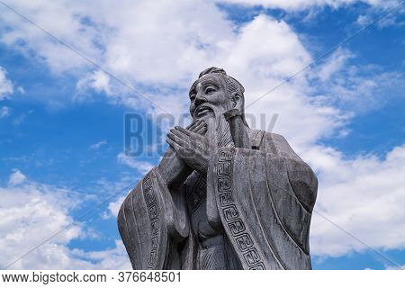 Confucius, Figurine Of Chinese Philosopher With Sky And Clouds