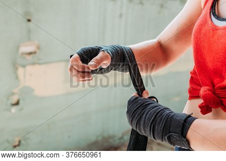 Close-up Of Fit, Young Woman Putting Boxing Wraps, Bandage On Her Hands. Boxing, Sport Activity