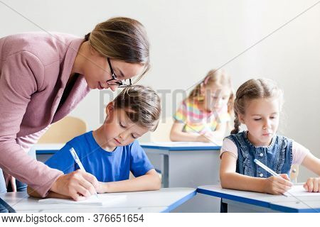 Teacher Helping Pupils Studying And Writing. Lesson For Kids At Elementary School. Children Sitting