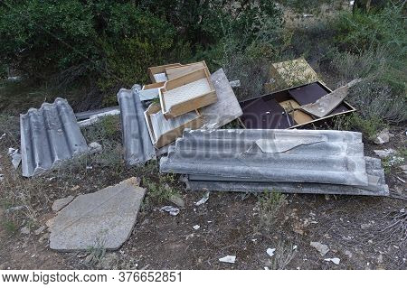 Asbestos Cement Corrugated Roofing Sheets And Broken Furniture Discarded In The Woods. Improper Disp