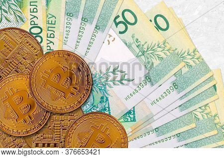50 Belorussian Rubles Bills And Golden Bitcoins. Cryptocurrency Investment Concept. Crypto Mining Or