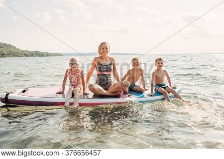 Caucasian Woman Parent Sitting On Paddle Sup Surfboard In Water With Kids Children. Modern Outdoor F