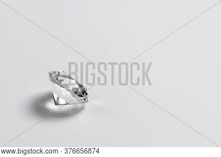 Dazzling Diamond On Neutral Light Background. Loose Brilliant Round Diamond Side View, Copyspace.
