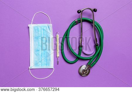 Top View Of Stethoscope, Mercury Thermometer And A Protective Face Mask On Colorful Background. Medi