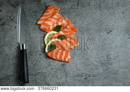 Fresh Raw Salmon Sashimi And Lemon Being Cut With A Knife And Lying On A Cutting Stone With Copy Spa