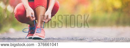 Exercise and sport running shoes runner woman tying laces getting ready for summer run in forest park panoramic banner header crop. Jogging girl exercise motivation heatlhy fit living.