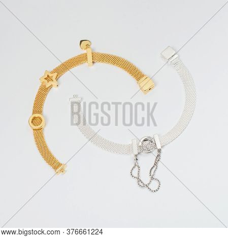 Silver And Gold Bracelets On White Background, Jewelry Flatlay On Neutral Background. Top View Of Fa