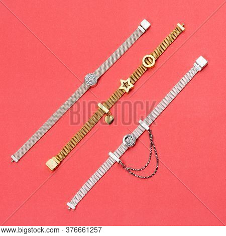 Silver And Gold Bracelets, Jewelry On Pink Background. Top View Of Fashion Luxury Woman Accessories,