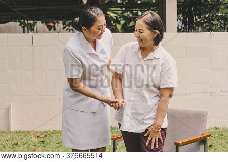 Smiling Nurse Helping Mature Elderly Who Knee Pain For Standing And Walking In A Nursing House. Nurs