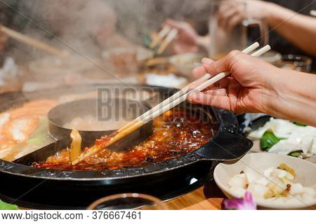 Woman Eating Vegetables With Chopsticks. Close Up Shot On Hot Pot