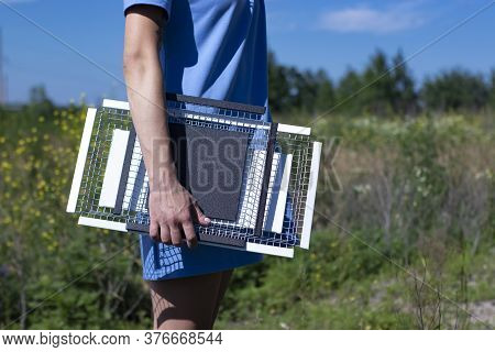 Girl In A Blue Dress Holds Two Handmade Metal Trays In The Field. No Face. Home Interior And Decor C