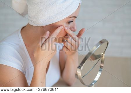 A Caucasian Woman With A White Terry Towel On Her Head Looks In The Mirror And Crushes Pimple. Probl