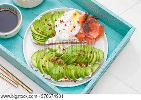 Bruschetta With Salted Salmon, Chopped Avocado, Pepper And Poached Egg On A White Plate On A Turqois