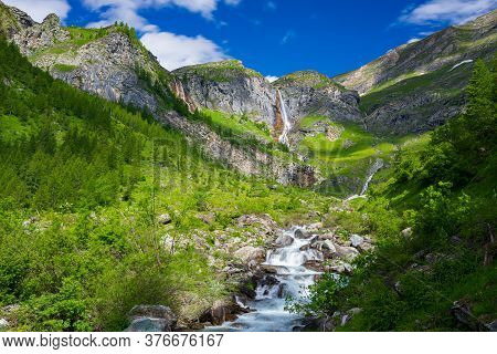 Scenic Waterfall And Mountain River On The Italian Alps. Tourism Destination Hiking Outdoors Activit