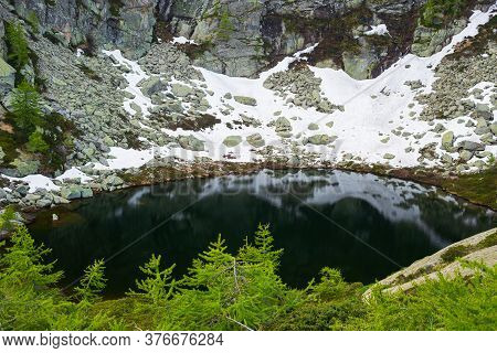 Alpine Lake In Idyllic Environment Amid Rocks And Forest. Natural Reservoir Of Fresh Water At High A