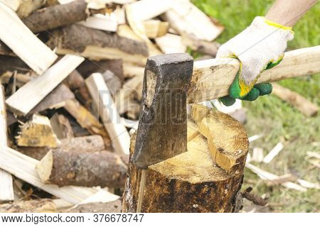 The Wood Chopper Sticks Out In Wooden Hemp. Ax And Ax Handle. Mans , Male Hands In White Colors Glov