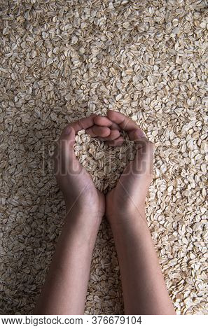 Cupped Teenager Hands With Rolled Oats In Shape Of Heart. There Is Some Natural Oat Flour On Fingers