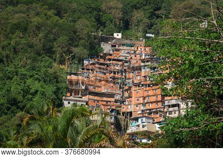 Stacked Red Brick Houses Of Brazilian Favela Surrounded By Tropical Forest In Rio De Janeiro, Brazil
