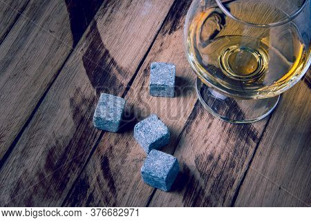 Whiskey Cooling Stones. Golden Whiskey In Glass With Cooling Stones On A Wooden Table