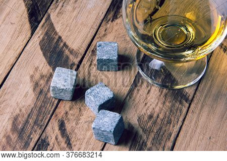 Glass Of Whiskey With Stones. Golden Whiskey In Glass With Cooling Stones On A Wooden Table