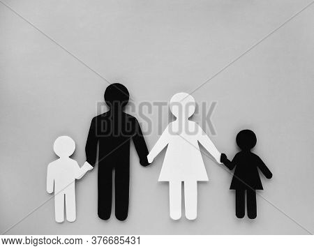 Symbol Of A Person And Family Cut Out Of Black And White Paper. Interracial Family. Space For Text.