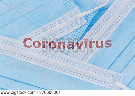 Coronavirus Word On A Heap Of Blue Surgical Face Masks - Coronavirus, Covid-19 Concept.