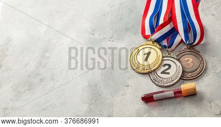 Doping Test. Gold, Silver And Bronze Medal And Test Tube With Blood On A Gray Background